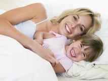 Mulher e rapariga no sorriso da cama fotografia de stock royalty free