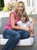 Mulher e rapariga que sentam-se no riso do pátio fotografia de stock