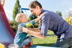 Mulher e rapaz pequeno que chuting abaixo da corrediça no campo de jogos Foto de Stock
