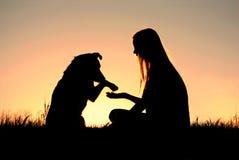 Mulher e seu cão que agitam a silhueta das mãos Fotografia de Stock Royalty Free