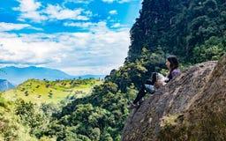 Mulher e seu cão que contemplam o horizonte em uma rocha, segundo pH fotos de stock