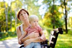 A mulher e seu neto da criança apreciam o dia ensolarado do outono Fotos de Stock Royalty Free
