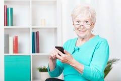 Mulher e smartphone idosos imagens de stock