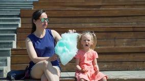 Mulher e sua filha bonito que comem o algodão doce video estoque