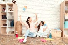A mulher e sua filha descansam após ter cansado a casa Sentam-se no assoalho com suas partes traseiras contra a parede e o resto imagens de stock