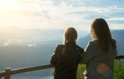 Mulher e sua filha que apreciam o nascer do sol da parte superior da montanha fotos de stock