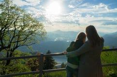 Mulher e sua filha que apreciam o nascer do sol da parte superior da montanha imagens de stock