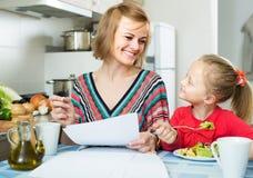 Mulher e sua filha que trabalham com papéis da casa fotografia de stock royalty free