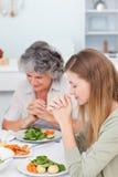 Mulher e sua matriz que praying na tabela Foto de Stock