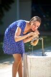 Mulher e torneira Fotos de Stock Royalty Free