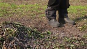 A mulher e uma criança limpam as folhas velhas secas no jardim vídeos de arquivo