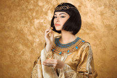 A mulher egípcia bonita gosta de Cleopatra com a garrafa de perfume no fundo dourado foto de stock royalty free
