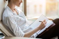 Mulher elegante alegre que escreve para baixo o comentário no jornal foto de stock
