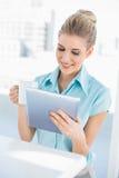 Mulher elegante alegre que usa a tabuleta que guardara o café Fotos de Stock