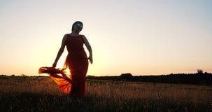 Mulher elegante animador em uma dança vermelha do vestido em um campo no por do sol no movimento lento filme