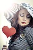 Mulher elegante bonita no chapéu que guarda o coração em suas mãos e manutenção programada Imagens de Stock