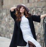 Mulher elegante bonita no ove preto na moda à moda do revestimento e do chapéu Imagem de Stock