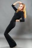 A mulher elegante bonita vestiu-se no preto elegante isolada sobre Imagens de Stock