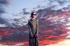 A mulher elegante da forma no vestido com a cópia do leopardo sobre o céu do por do sol da noite com nuvens ajardina Imagem de Stock