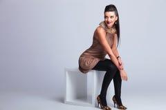 Mulher elegante da forma que senta-se em uma cadeira ao sorrir foto de stock royalty free