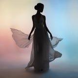 Mulher elegante da silhueta no vestido de sopro foto de stock