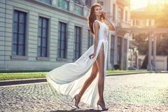 Mulher elegante de Beautifilul no passeio lisonjeiramente branco longo do vestido Imagens de Stock Royalty Free