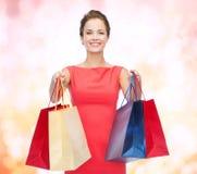 Mulher elegante de sorriso no vestido com sacos de compras Imagens de Stock Royalty Free