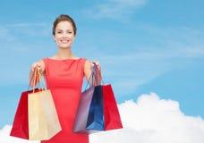 Mulher elegante de sorriso no vestido com sacos de compras Fotografia de Stock Royalty Free