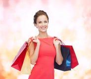 Mulher elegante de sorriso no vestido com sacos de compras Foto de Stock Royalty Free
