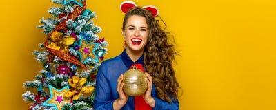 Mulher elegante de sorriso que guarda a bola do Natal Imagens de Stock Royalty Free