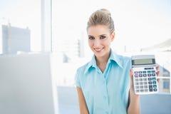 Mulher elegante de sorriso que mostra a calculadora Foto de Stock