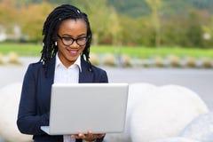 Mulher elegante de sorriso que usa o portátil Imagem de Stock