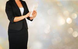 A mulher elegante de Younf no terno de negócio que guarda a tabuleta na frente do bokeh do glamourus ilumina o fundo Imagem de Stock Royalty Free