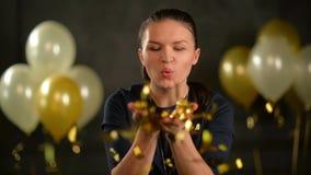 A mulher elegante está fundindo em confetes essa lentamente queda para baixo Morena durante a celebração no estúdio sobre o preto vídeos de arquivo