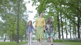 Mulher elegante madura que anda no parque com suas duas netas M?os felizes da terra arrendada da fam?lia Despesa da avó filme