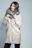 Mulher elegante no revestimento, no lenço de lã e no chapéu levantando no estúdio sobre o fundo cinzento Fotografia de Stock Royalty Free