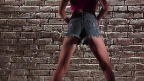 A mulher elegante no short da parte superior e da sarja de Nimes da colheita dança o twerk contra uma parede de tijolo Movimento  filme
