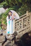 Mulher elegante no umberalla tradicional chinês do papel da posse do vestido do hanfu em uma ponte de pedra imagens de stock
