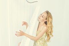 Mulher elegante no vestido do ouro com o cabelo louro longo que joga a harpa, no fundo branco Imagens de Stock Royalty Free