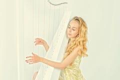 Mulher elegante no vestido do ouro com o cabelo louro longo que joga a harpa, no fundo branco Imagem de Stock