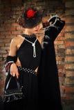 Mulher elegante no vestido e no chapéu pretos com véu Fotos de Stock Royalty Free