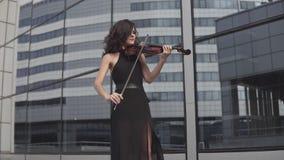 Mulher elegante no vestido preto que joga o violino perto da construção de vidro Conceito da arte vídeos de arquivo