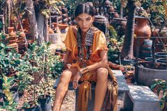 A mulher elegante nova bonita com comp?e e os acess?rios ? moda do boho que levantam no fundo tropical natural foto de stock royalty free