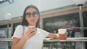 Mulher elegante nova feliz que toma uma ruptura de café após a compra, sorrindo com café-à-ir em suas mãos contra video estoque