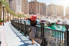 A mulher elegante olha Marina Walkway em Porto Arábia na pérola em Doha fotos de stock royalty free