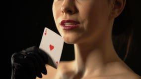 Mulher elegante que afaga sua cara com o ás de corações, sinal da fortuna, jogando video estoque