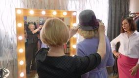 Mulher elegante que escolhe o chapéu à moda no vendedor dianteiro do espelho do boutique da forma junto Mulher madura que tenta o filme