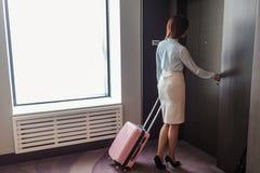 Mulher elegante que fala no telefone esperto ao sair do hotel com a mala de viagem imagem de stock royalty free