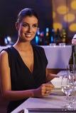 Mulher elegante que senta-se na tabela de comensal Imagem de Stock