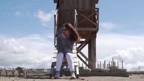A mulher elegante senta-se pela torre e pelos olhares do salvamento no mar video estoque